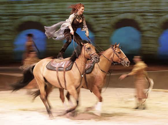 Fairland Ferguson rides while standing on the backs of a pair of horses during a dress rehearsal for the show