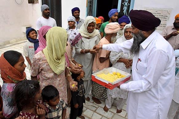 Residents of Jatti Umra, native village of Pakistan`s former prime minister Nawaz Sharif, distribute sweets as they celebrate Sharif's election victory at Jatti Umra, near Amritsar, India.