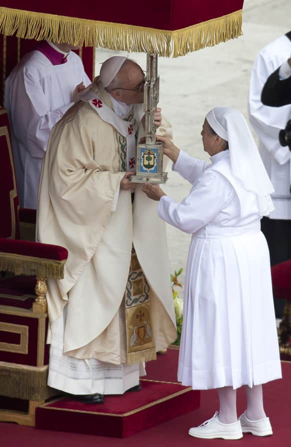 Pope Francis kisses a cross containing relics of Maria Guadalupe Garcia Zavala during the canonization ceremony in St. Peter`s Square at the Vatican.
