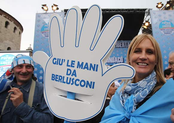 Silvio Berlusconi`s supporters hold a cutout hand reading