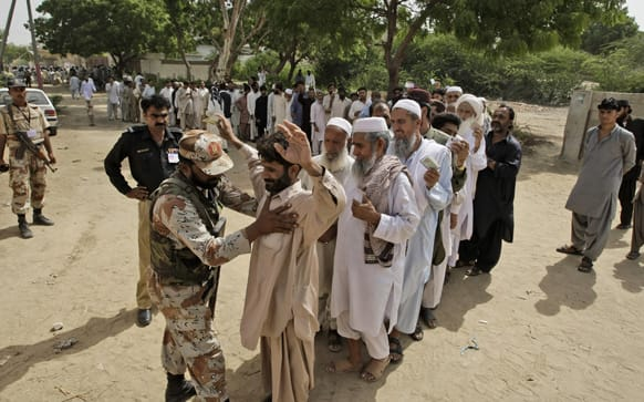 A Pakistani paramilitary soldier checks voters before they enter a polling station to cast their ballots, in Karachi, Pakistan.