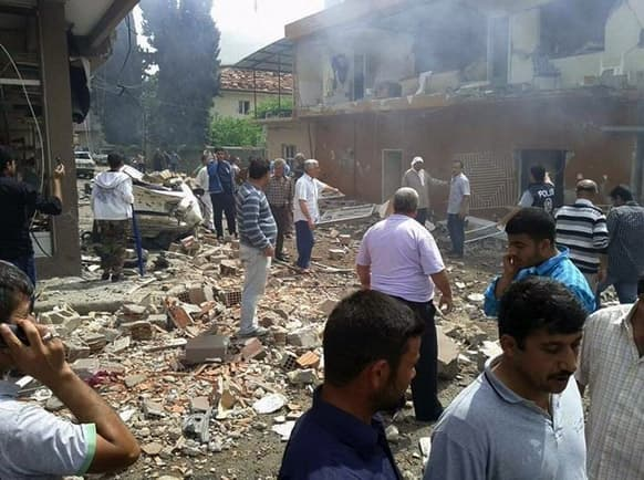 People gather at the site of a blast which killed and injured a number of people in Reyhanli, near Turkey`s border with Syria. Two car bombs exploded in a Turkish town near the border with Syria on Saturday, killing at least four people and injuring 22 others.