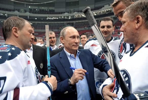 Russian President Vladimir Putin, center, signs autographs after an ice hockey match during a festival of Russia`s amateur hockey in the Bolshoy ice dome, the hockey venue for the Sochi 2014 Winter Olympics, in the Olympic Park in Adler.