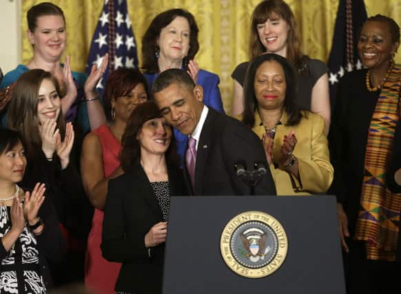 President Barack Obama, center, is introduced by Carol Metcalf, left, before speaking about the Affordable Care Act in the East Room of the White House in Washington.