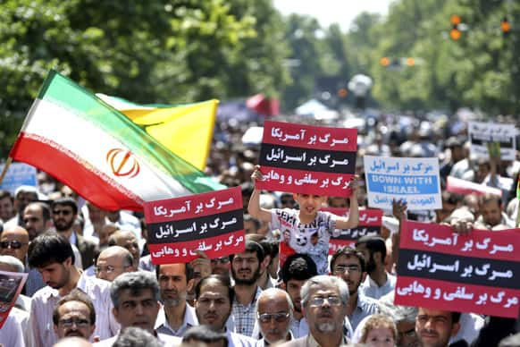 Iranians attend a demonstration against Iraeli air strikes in Syria after Friday prayers, in Tehran, Iran.