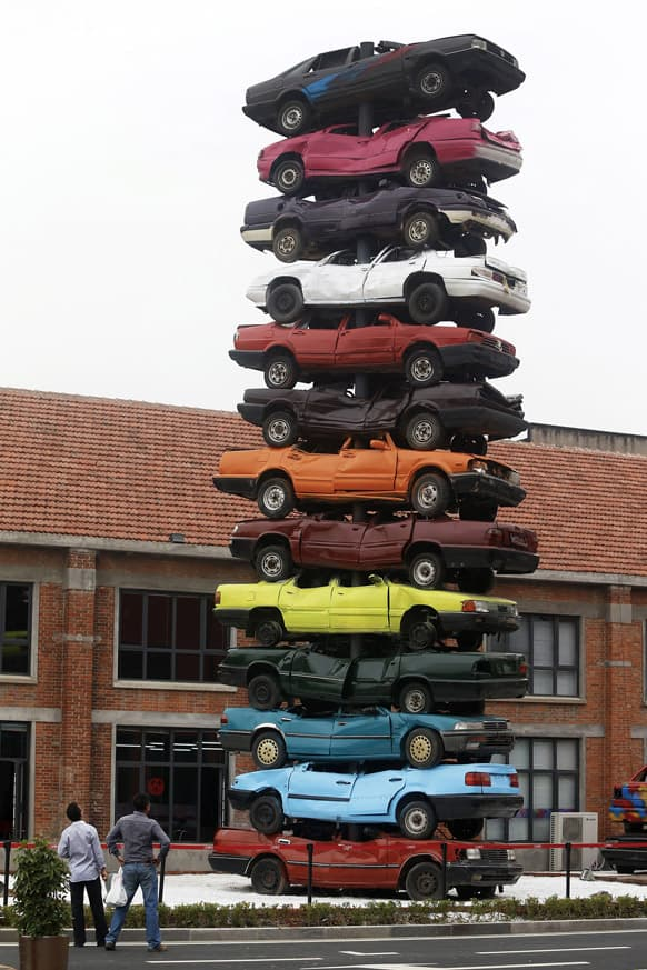 Visitors look at an art form made by piles of colorful scraped cars, entitled