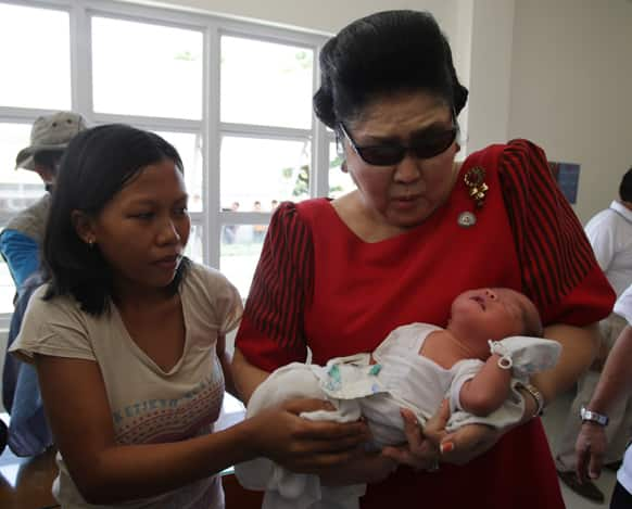 Former Philippine First Lady Imelda Marcos, right, reacts as she carries a baby at a