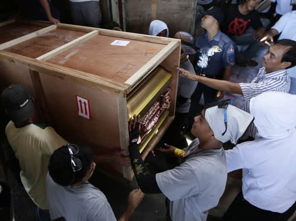 Airport workers load the casket of Vasco Jurian Stelter, 35, a German national and one of four foreigners killed in Tuesday`s eruption of Mayon volcano in Albay province in central Philippines, upon arrival in Manila.