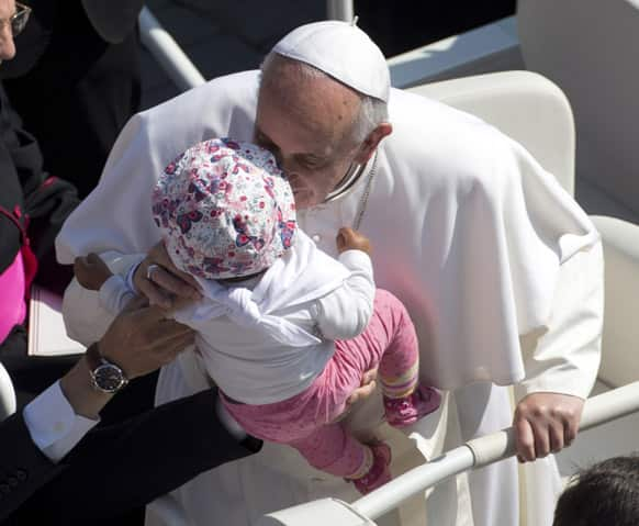 Pope Francis kisses a baby as he arrives in St. Peter`s Square at the Vatican for his weekly general audience.