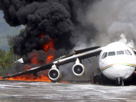 Smoke billows from a British-made BAe 146 cargo plane that caught fire while being unloaded at the airport in Wamena, Papua province, Indonesia.