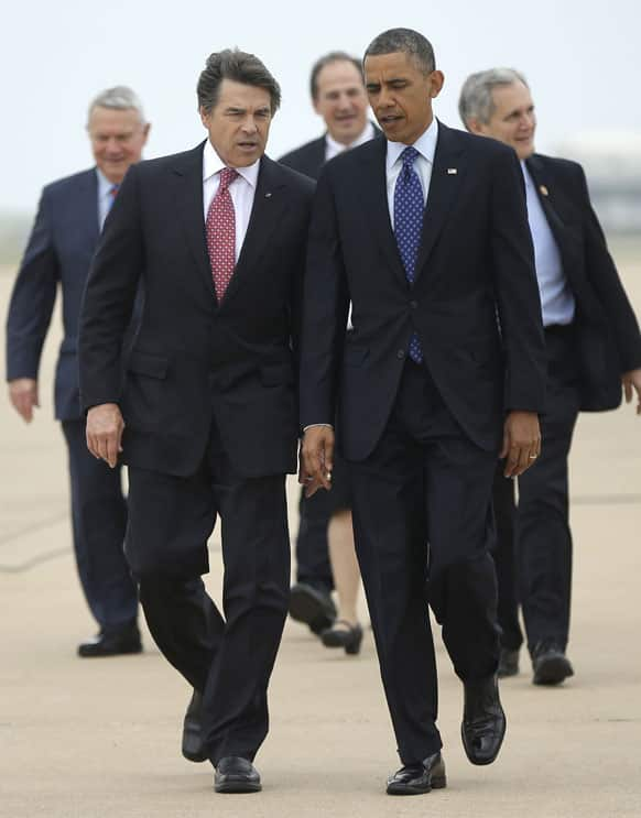 President Barack Obama, right, talks with Texas Gov. Rick Perry, left, as the walk on the tarmac during his arrival on Air Force One at Austin-Bergstrom International Airport.
