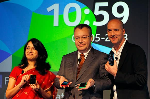 Nokia`s Chief Executive Officer Stephen Elop, center, head developer Sangeeta Bavi, left, and design head Peter Skillman display Nokia Asha 501 smartphones during its launch in New Delhi. Nokia unveiled the first of a new family of Asha smartphones with the Nokia Asha 501 priced at US$99.