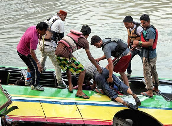 Rescuers take out a body from a bus that plunged into the Beas River near Kullu, India.