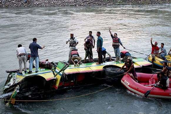 Rescuers look for survivors after a bus plunged into the Beas River near Kullu, India.