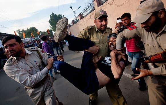 Policemen detain a Kashmiri government employee during a protest in Srinagar.