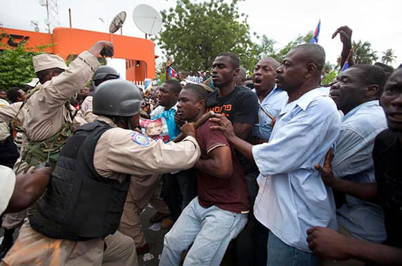 Police use batons to push back supporters of Haiti`s former President Jean-Bertrand Aristide as Aristide leaves the courthouse in Port-au-Prince, Haiti.