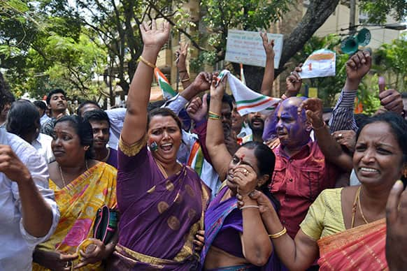 Congress party supporters celebrate outside a counting station after hearing news of the party leading in the recently held state elections in Bangalore.