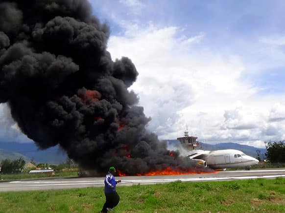 Smoke billows from a British-made BAe 146 cargo plane that caught fire while being unloaded on the tarmac at the airport in Wamena, Papua province, Indonesia. An official said that the plane caught fire after a drum of oil fell from the aircraft and somehow sparked the fire.