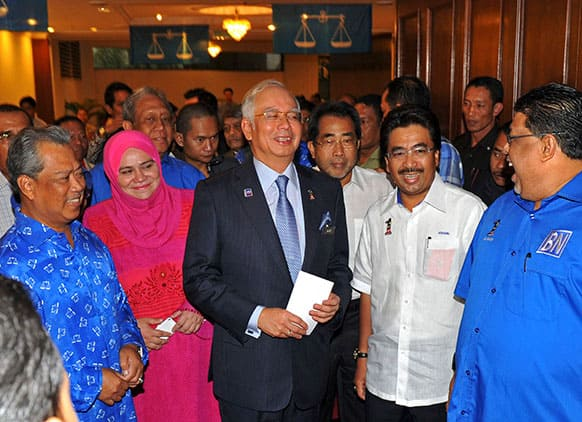 Malaysian Prime Minister Najib Razak, center, smiles as he arrives during a meeting with his ruling National Front coalition`s members of parliament in Kuala Lumpur, Malaysia.