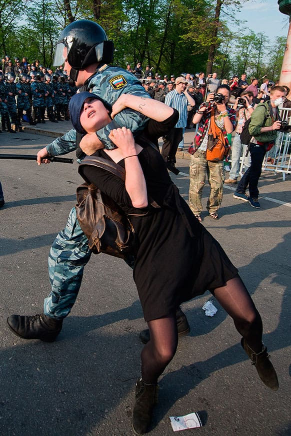 A Russian police officer detains protester Alexandra Dukhanina during an opposition rally in Moscow.