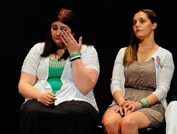 Hannah D`Avino, sister of Sandy Hook Elementary School shooting victim Rachel D`Avino, left, wipes a tear as Erica Lafferty, daughter of principal Dawn Hochsprung, right, looks on during a ceremony awarding the families the citizen honor of the Congressional Medal of Honor on behalf of in Newtown.