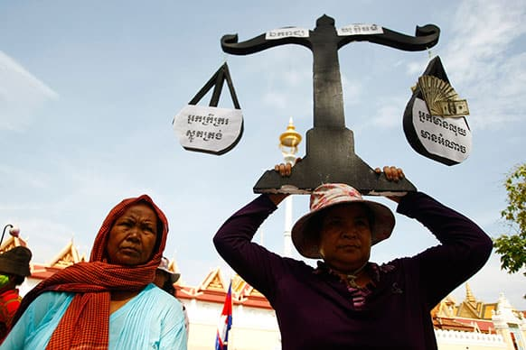 A protester from Boeung Kak lake holds a cutout of a scale symbolizing justice as she joins other villagers, who were allegedly evicted from their homes without adequate compensation, during a rally in front of the Justice Ministry in Phnom Penh, Cambodia.