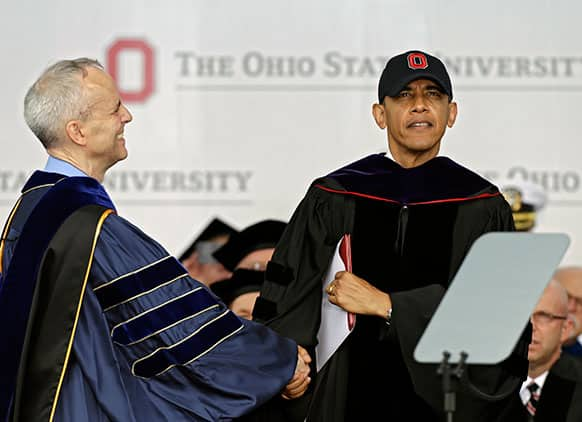 President Barack Obama is congratulated by David Horn, left, after receiving an honorary doctor of law degree at Ohio State University`s spring commencement  in Columbus, Ohio.