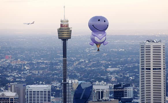 A hot air balloon from a fruit juice company flies over Sydney Harbour and along the Sydney skyline as a commercial jet flies past in the back.