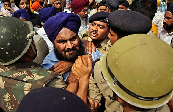 Police try to stop a Sikh protester as he protests the acquittal of ruling Congress party leader Sajjan Kumar of charges that he incited mobs to kill Sikhs during the country`s 1984 anti-Sikh riots in New Delhi.