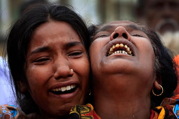 A woman is comforted as she grieves after identifying the body of her daughter, a victim of the garment factory collapse, Sunday, May 5, 2013 in Savar, near Dhaka.