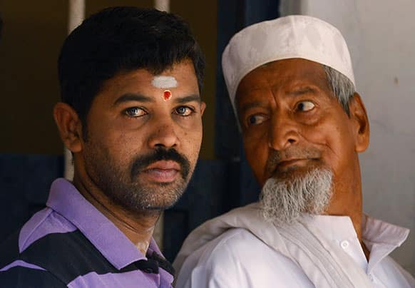 An Indian Muslim, right, stares at a Hindu man as they wait outside a polling station to caste their votes in Bangalore.