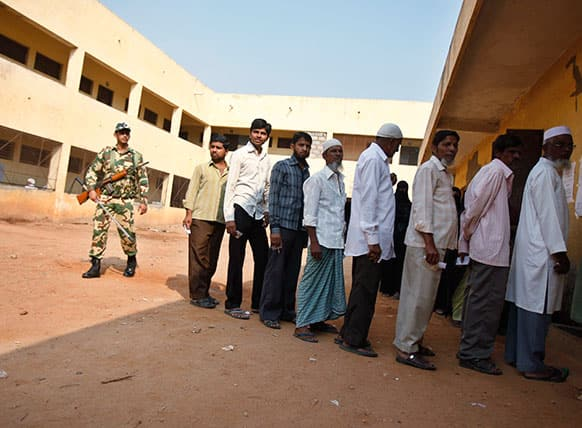 An Indian paramilitary soldier stands guard as voters line up outside a polling station to caste their votes in Bangalore.