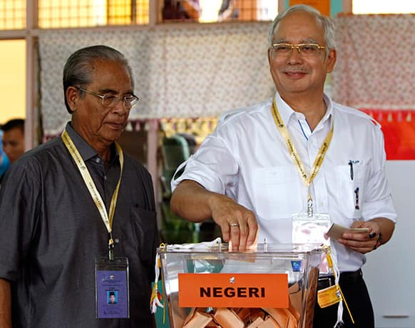 Malaysian Prime Minister Najib Razak, right, casts his ballot in the general elections at a polling station in Pekan, Pahang state, Malaysia.