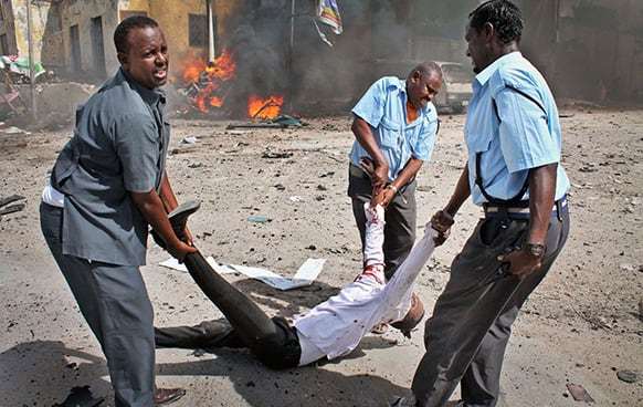 Somali security force members carry away a severely wounded man following a suicide car bomb blast in the capital Mogadishu, Somalia.