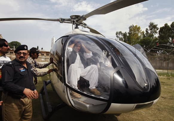 Pakistan`s former cricket star-turned-politician Imran Khan gestures from inside a helicopter as he prepares to leave after addressing an election campaign rally in Charsadda, Pakistan.