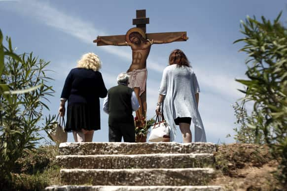 Worshippers pay homage to a giant wooden crucifix during a Good Friday reenactment of Christ being taken down from the cross, at the Pendeli Monastery, near Athens. Orthodox Christians around the world celebrate Easter on Sunday, May 5.
