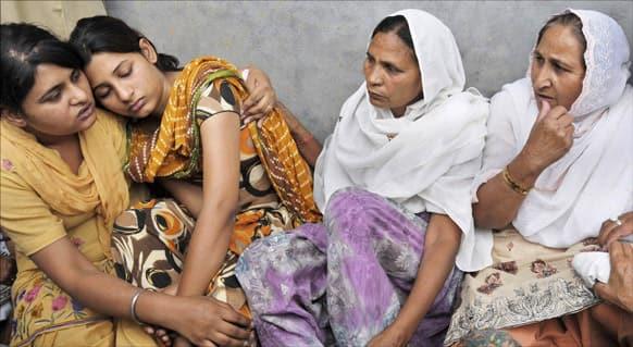 Wife Sukhpreet Kaur, sister Dalbir Kaur and Poonam and Swapandeep, daughters of Sarabjit Singh, mourn during his funeral at Bhikhiwind.