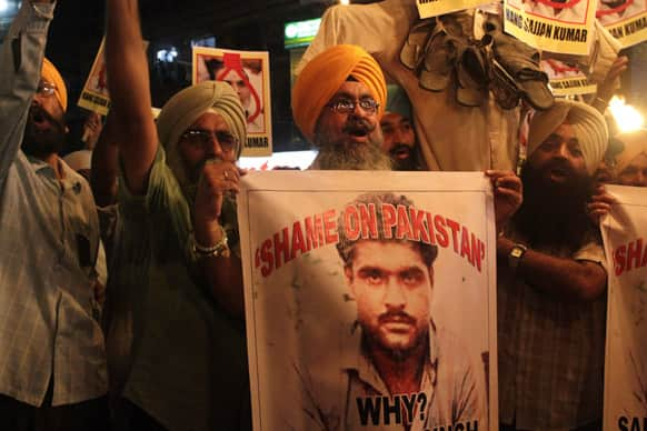 Sikhs shout slogans against Pakistan as they display photographs of Sarabjit Singh during a protest in Kolkata.