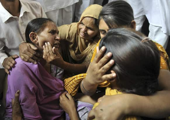 Relatives try to console Sukhpreet Kaur, wife of Sarabjit Singh, a convicted Indian who died after he was bludgeoned to death by two fellow inmates at a Pakistani prison as she and her daughters react to the news at Bhikhiwind.