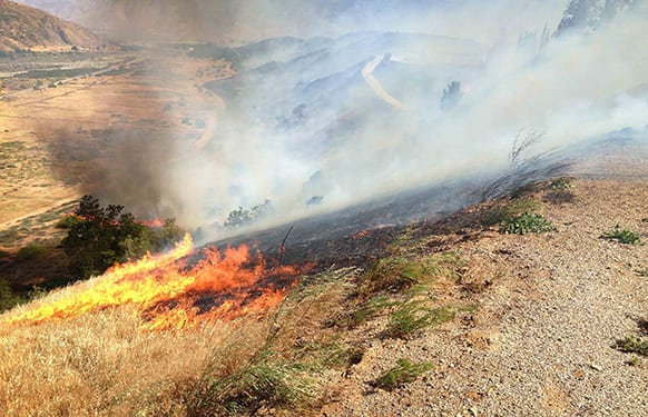 Flames scorch the hillside north of Banning, Calif., as a brush fire burns in the area.