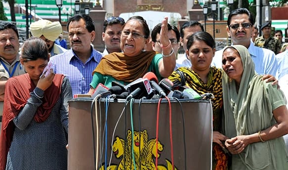 Dalbir Kaur, sister of Sarabjit Singh, an Indian spy on death row in Pakistan, addresses the media as Singh's wife Sukhpreet Kaur, right, and daughters Poonam, left, and Swapandeep, second from right, stand beside her after entering Indian soil at the India-Pakistan border area of Wagah, India.