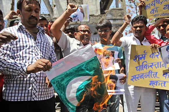 Indians shout slogans against the Pakistan government and burn their national flag during a protest against an attack on an Indian prisoner in a Lahore prison, in Ahmadabad, India.