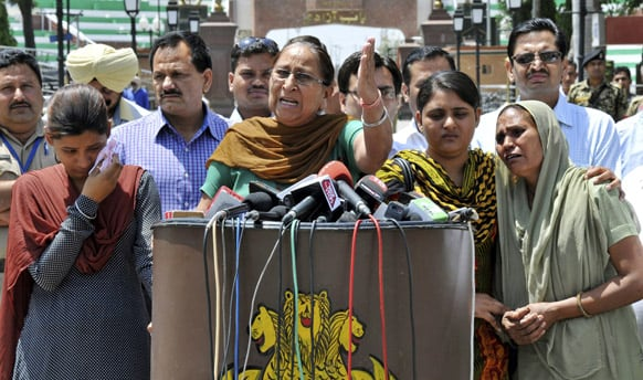 Dalbir Kaur, sister of Sarabjit Singh, addresses the media as Singh's wife Sukhpreet Kaur and daughters stand beside her after entering Indian soil at the India-Pakistan border area of Wagah, India.