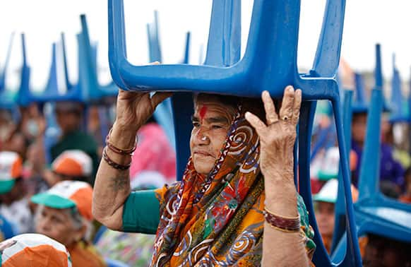 An elderly Congress party supporter holds a chair to shield herself from rain as she waits with others for Indian Prime Minister Manmohan Singh at a campaign rally for the upcoming Karnataka state election on the outskirts of Bangalore.