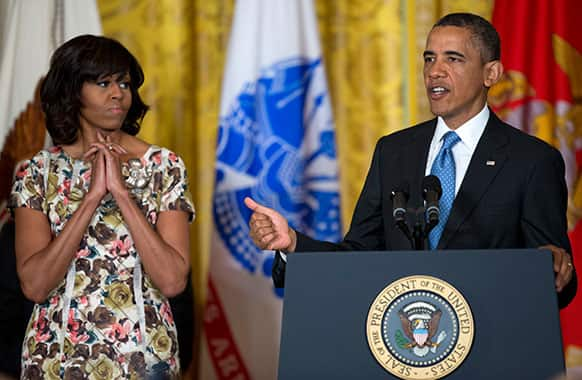 First lady Michelle Obama listens at left as President Barack Obama speaks during an event to promote hiring military veterans, in the East Room of the the White House.