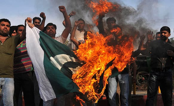 Indian youths protest against the attack on Indian prisoner Sarabjit Singh at a jail in Lahore burn a Pakistani flag and shout slogans in Amritsar.
