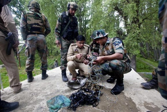 Soldiers and police officer, inspect the parts after detecting and defusing a bomb on the outskirts of Srinagar.