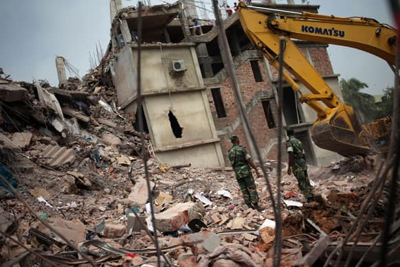 Army personnel watch as workers toil in the collapsed garment factory building.