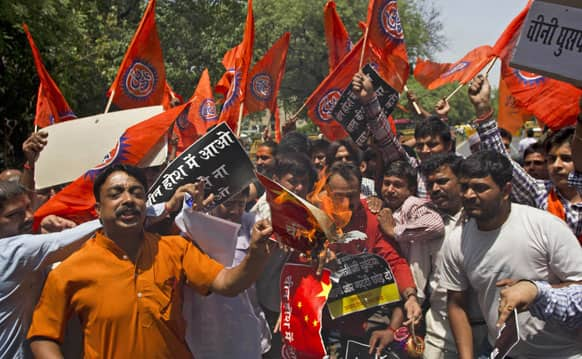 Bharatiya Janata Party youth wing activists burn a Chinese flag during a protest against the alleged incursion by Chinese troops into Indian territory in New Delhi.