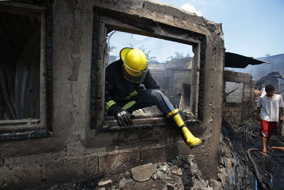 A fireman comes out the window of a burned house after it caught fire together with about 100 homes in suburban Quezon city, north of Manila, Philippines.